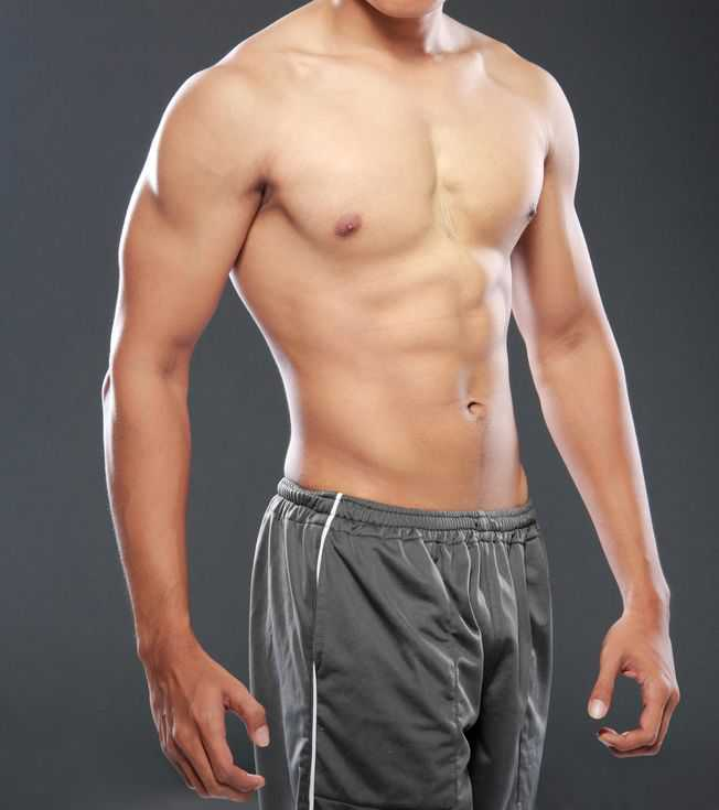 20599585 - a young and fit male model posing his muscles
