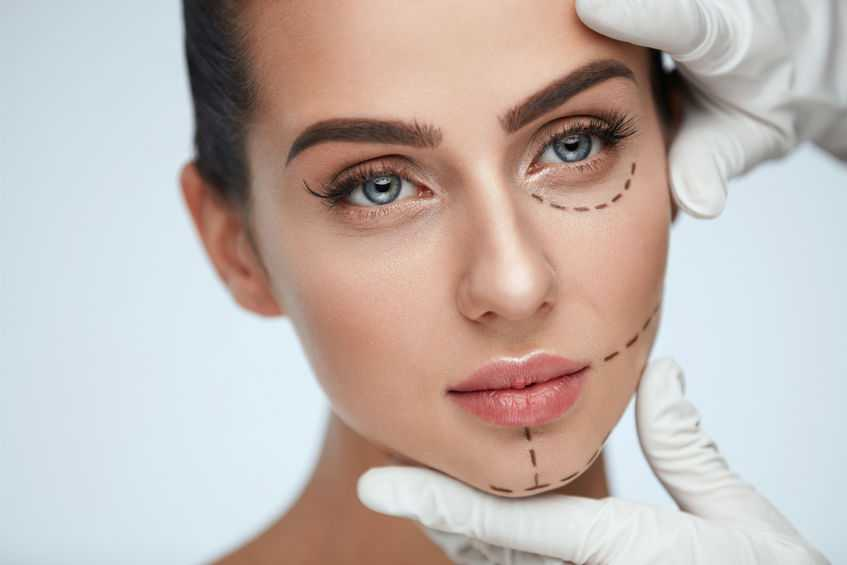Facial Beauty Treatment. Beautiful Young Female With Smooth Skin, Perfect Makeup And Surgical Lines. Closeup Of Beautician Hands Touching Woman Face Before Plastic Surgery Operation. High Resolution